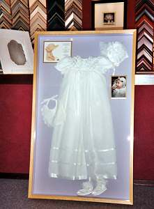Shadow box frame with christening dress.